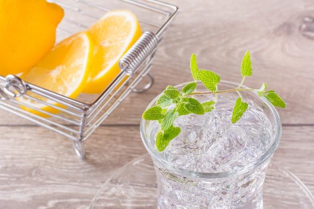 Освежающая минеральная вода с кубиками льда и листьями мяты в прозрачном стакане и дольками лимона в корзине на деревянном столе