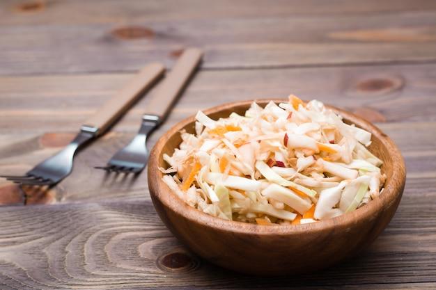 キャベツ、セロリ、ニンジン、リンゴの木製のプレートと木製のテーブルのフォークのアメリカのすぐに食べられるコールスローサラダ。