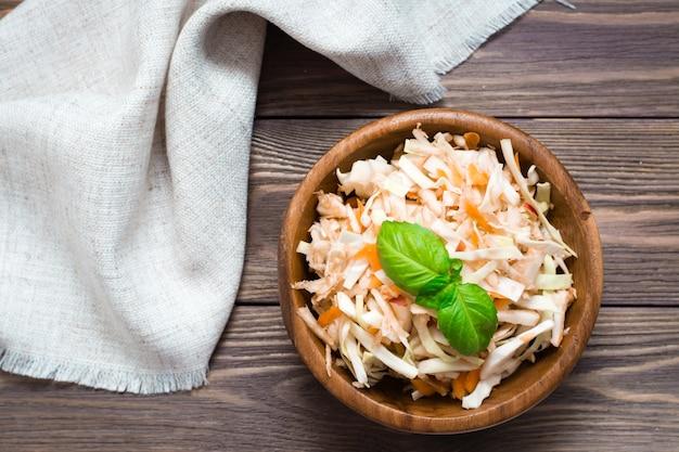 Американский готовый к употреблению салат из капусты капусты, сельдерея, моркови и яблок с листьями базилика в деревянной тарелке и вилками на деревянном столе.