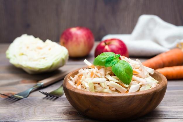 Американский готовый к употреблению салат из капусты капусты из капусты, сельдерея, моркови и яблок с листьями базилика в деревянной тарелке и ингредиенты для приготовления пищи на деревянном столе.