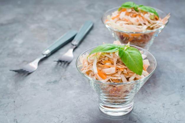 Американский готовый к употреблению салат из капусты капусты, сельдерея, моркови и яблок с листьями базилика в стеклянных мисках на столе.