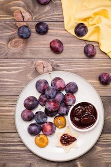 Аппетитная брускетта из свежего хлеба со сливовым вареньем и спелыми ягодами синей сливы на тарелке на дровах