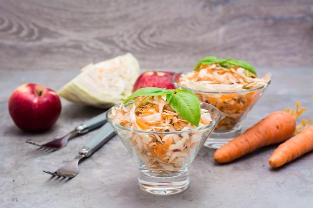 Американский готовый к употреблению салат из капусты капусты, сельдерея, моркови и яблок с листьями базилика в стеклянных мисках в ингредиентах для приготовления пищи на столе.