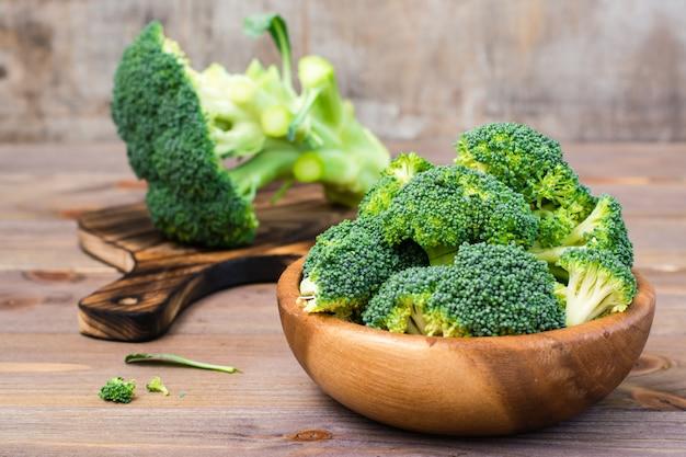 新鮮な生のブロッコリーを食べる準備ができて、木製のテーブルの上の木製プレートの花序に分かれています。