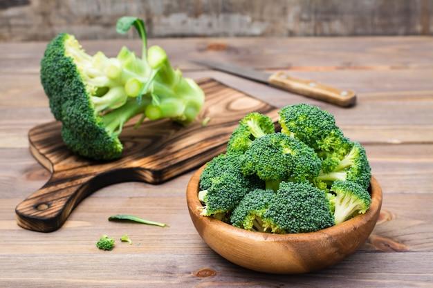 新鮮な生のブロッコリーを食べる準備ができて、木製のプレートとまな板と木製のテーブルにナイフで花序に分かれています。