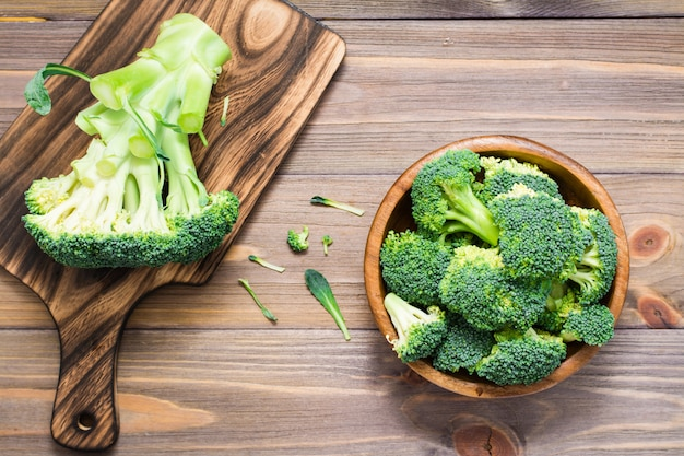 新鮮な生のブロッコリーを食べる準備ができては、木製のプレートと木製のテーブルのまな板の上の花序に分かれています。