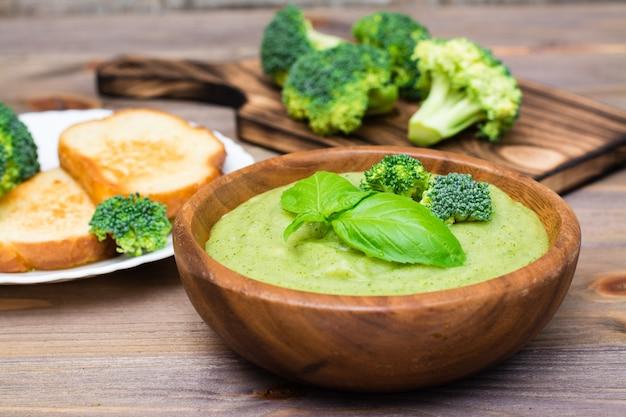 ブロッコリーとバジルの部分と新鮮な熱いブロッコリーのピューレスープを食べる準備ができて、木製テーブルの上の木製プレートに残します。