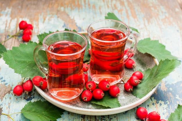 ウッドテーブルの上の透明なガラスのサンザシの果実から熱いお茶