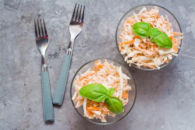 キャベツ、セロリ、ニンジン、バジルとリンゴのアメリカのすぐに食べられるコールスローサラダは、テーブルで調理するための食材のガラスのボウルに残します。健康的で適切な栄養の概念。