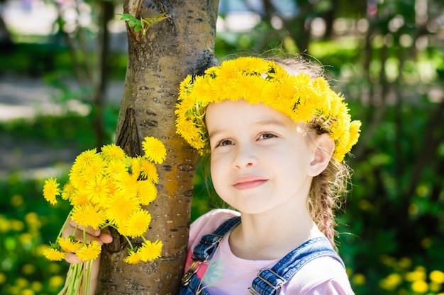 タンポポの花輪と公園で散歩に彼女の手でタンポポの花束とかわいい女の子