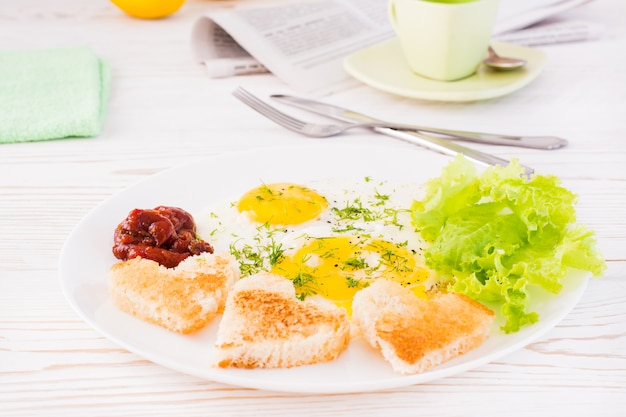スクランブルエッグ、揚げパン、ケチャップ、レタスをテーブルの上の皿に残します。すぐに食べられる朝食