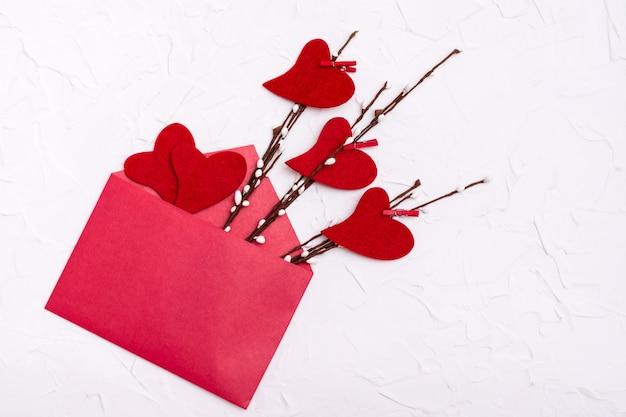 バレンタイン・デー。柳の枝と開いた赤い封筒に近いフェルトで作られた赤いハート。コピースペース