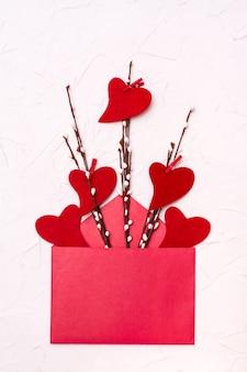 バレンタイン・デー。柳の枝と開いた赤い封筒の近くにフェルトで作られた赤いハート
