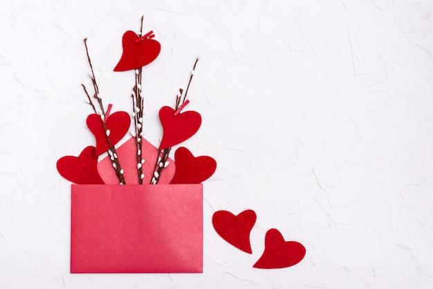 バレンタイン・デー。開いた赤い封筒の近くの柳の枝にフェルトで作られた赤いハート。コピースペース