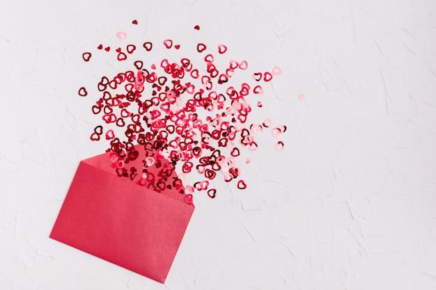 バレンタイン・デー。開いた赤い封筒から赤い明るいハートが飛び出します。コピースペース