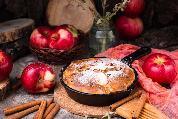 鉄鍋にりんごを詰めたパイ。木製のテーブルに熟したリンゴ。
