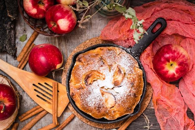 鉄鍋にりんごを詰めたパイ。木製のテーブルに熟したリンゴ。上面図