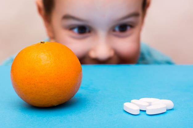 Белые овальные таблетки и спелый апельсин лежат на лице ребенка на синем.