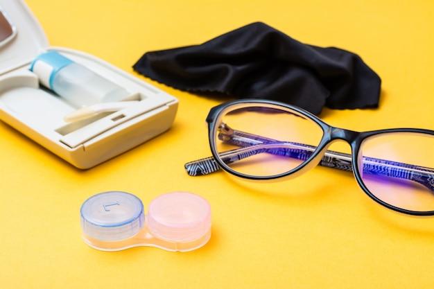 レンズを収納するためのアクセサリー:容器、ケースに入った液体のボトル、ピンセット、メガネと布