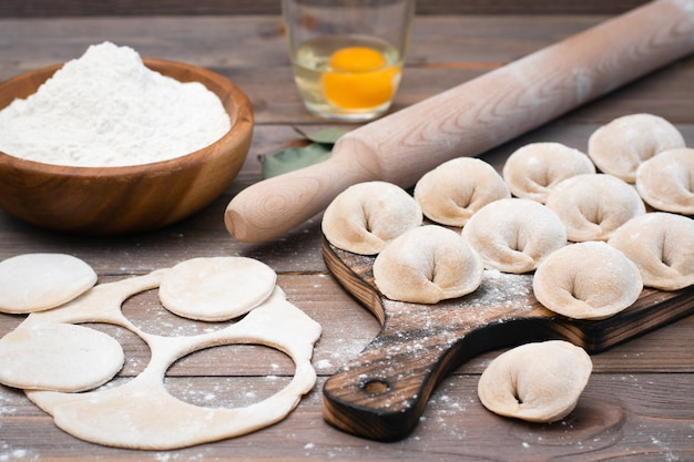 餃子や木製のテーブルで調理するための食材を成形するプロセス