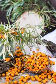 木製のテーブルの上にボウルに海クロウメモドキの果実