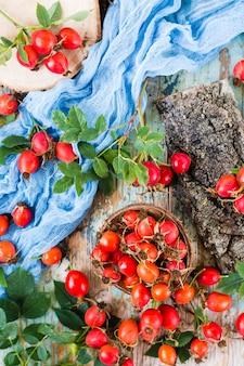 木製のテーブルの上にボウルにドッグローズの果実。上面図