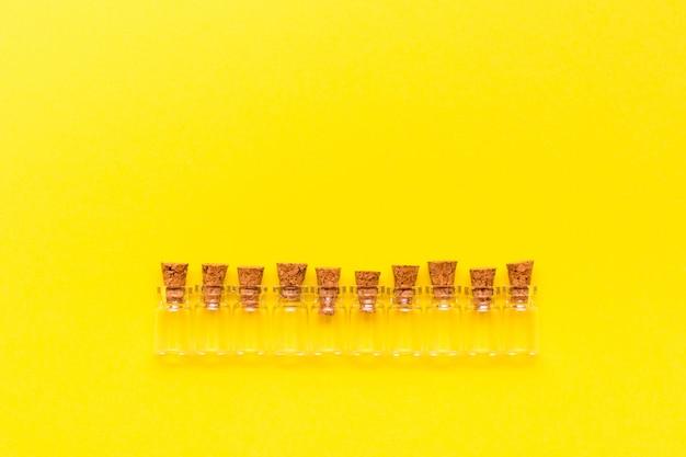 黄色の背景に並んで配置されたストッパー付きの小さな空の透明なボトル。上面図