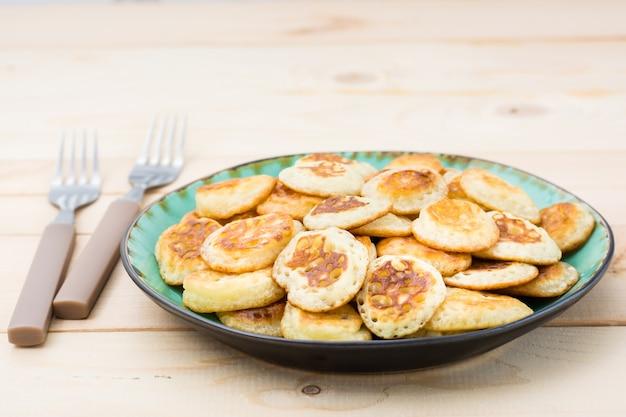 Тренд завтрак. голландские мини-блины на тарелку и две вилки на деревянном столе.