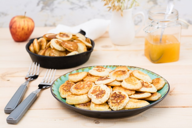 Тренд завтрак. голландские мини блины на тарелку и сковорода с ними на деревянном столе.