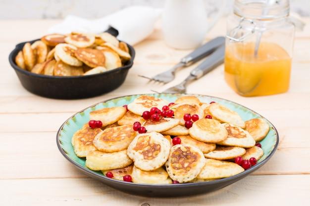 Тренд завтрак. голландские мини блины с красной смородиной на тарелку и сковороду с ними на деревянном столе.