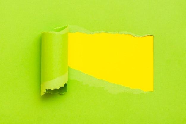 背景が黄色のテキスト用のスペースと引き裂かれた緑の紙