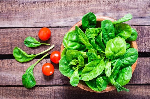 Свежие листья шпината в миску и помидоры черри на деревянном столе
