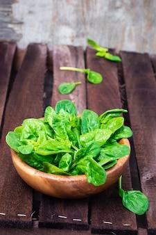 木製のテーブルの上にボウルにほうれん草の新鮮な葉