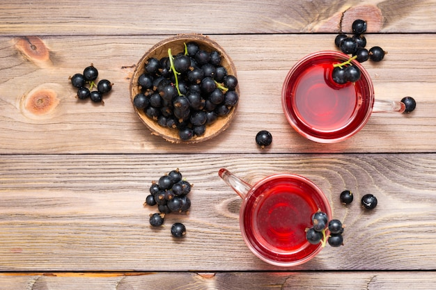 ガラスと木製のテーブルの上の果実のボウルで新鮮な熟した黒スグリのコンポート