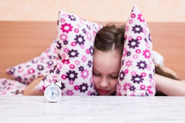 白い目覚まし時計は、枕で耳を覆う少女の背景のテーブルの上に立つ