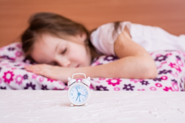 眠っている少女の背景のテーブルの上に白い目覚まし時計が立っています。