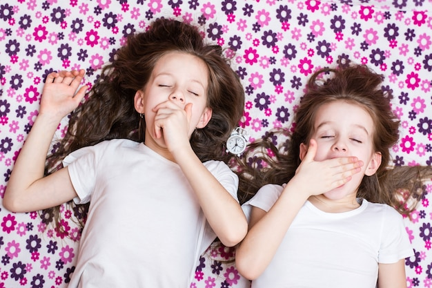 Две просыпающиеся зевающие девочки и будильник между ними. вид сверху