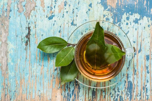 木製の素朴なテーブルの上にカップで月桂樹の葉から新鮮なお茶。上面図