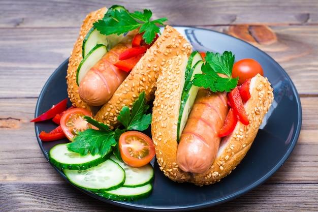 Аппетитные хот-доги из жареных колбасок, кунжутных булочек и свежих овощей на тарелке на деревянном столе