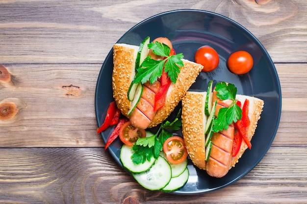 木製テーブルの上の皿に揚げたソーセージ、ごまパン、新鮮な野菜から出来上がったホットドッグ。上面図