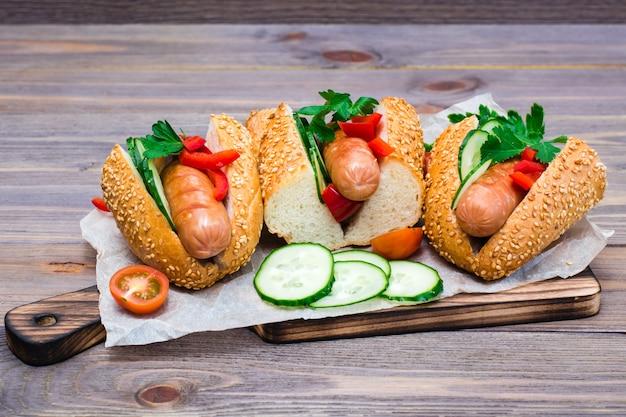 木製テーブルのまな板の上で揚げたソーセージ、ゴマパン、新鮮な野菜の食欲をそそるホットドッグ