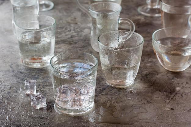 滴と氷のかけらがはねた灰色のテーブルの上の水の多くのグラス