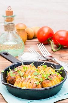 木製テーブルの上の鉄鍋でルッコラとスパイスとオイルで焼き若いジャガイモ