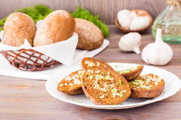 木製のテーブルプレート上のディルと新鮮なライ麦ガーリッククルトン