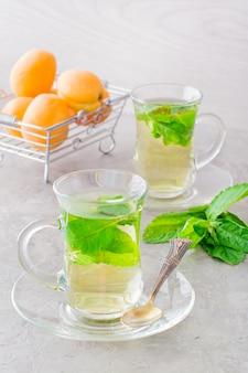 テーブルの上の透明なガラスのミントの葉と熱いお茶