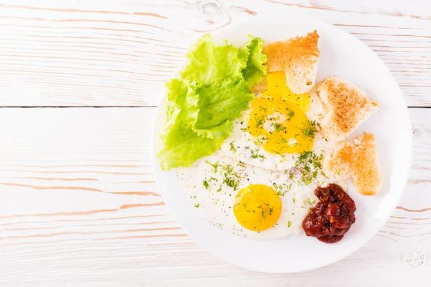 テーブルの上の皿にスクランブルエッグ、揚げパン、ケチャップ、レタスの葉