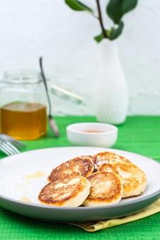 木製テーブルの上の皿に蜂蜜と自家製カッテージチーズのパンケーキ