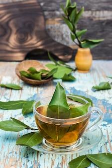 Свежий чай из лаврового листа в чашке на деревянном деревенском столе