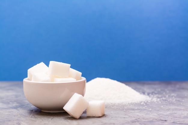 ボウルに入れた洗練された砂糖の断片と砂糖の山