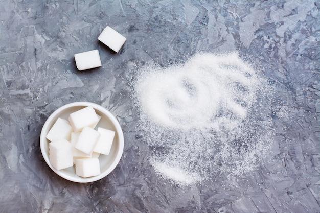 ボウルに洗練された砂糖の断片とテーブルの上の砂糖砂の山